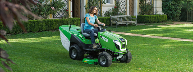 Une dame coupe la pelouse avec un tracteur tondeuse